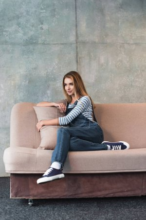 Photo for Young beautiful woman posing, hugging pillow and sitting on pink sofa - Royalty Free Image