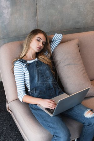 Photo pour Jeune fille belle, rêvant sur un canapé rose avec ordinateur portable - image libre de droit