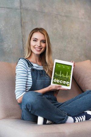 Photo pour Jeune femme assise sur le canapé et écran d'affichage de la tablette numérique - image libre de droit
