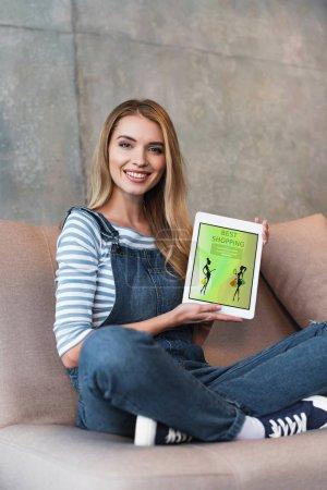 Photo pour Belle femme assise sur le canapé et écran d'affichage de la tablette numérique - image libre de droit