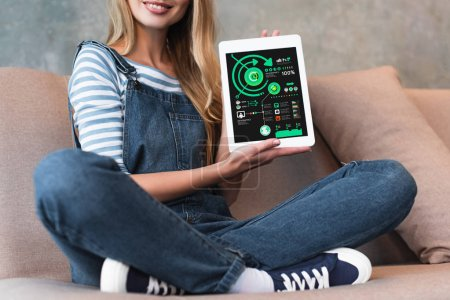 Photo pour Jeune fille assise sur le canapé et écran d'affichage de la tablette numérique vue recadrée - image libre de droit