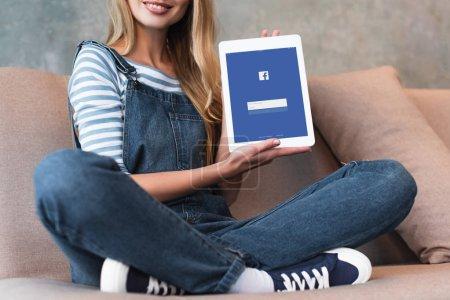 Photo pour Recadrée vue de jeune fille assise sur le canapé et écran de projection avec facebook - image libre de droit