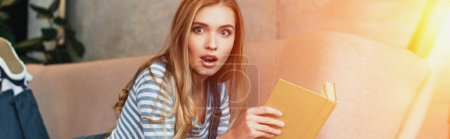 shocked young woman in room with sunshine holding book in hands