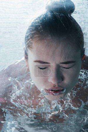 Photo pour Gros plan de jeune femme pose sous l'eau avec les yeux fermés - image libre de droit