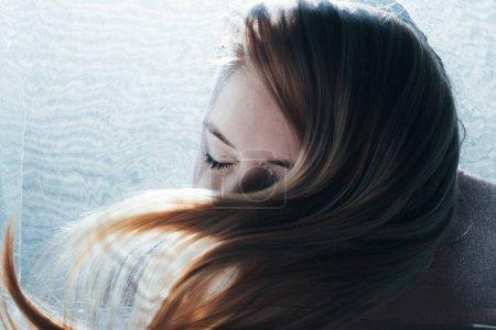 Photo pour Vue recadrée de belle fille adulte posant sous l'eau avec les yeux fermés - image libre de droit