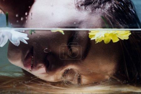 Photo pour Gros plan de belle fille posant sur l'eau avec des fleurs - image libre de droit