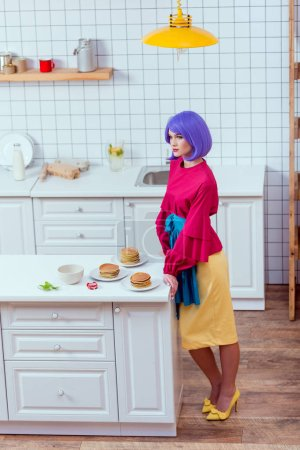 Photo for Housewife with purple hair and colorful clothes posing near kitchen counter with pancakes - Royalty Free Image