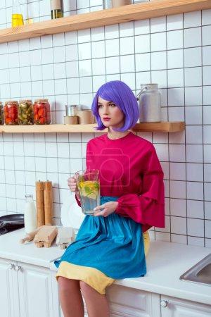 Hausfrau mit lila Haaren und bunten Kleidern sitzt auf der Küchentrese mit hausgemachter Limonade im Glas