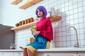 serious housewife with purple hair and colorful clothes sitting on kitchen counter and holding glass jar with lemonade