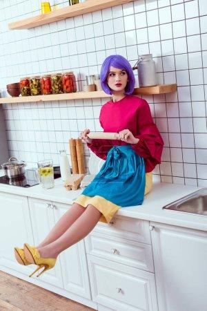 Photo pour Femme au foyer avec des cheveux violet assis sur le comptoir de cuisine avec le rouleau à pâtisserie - image libre de droit