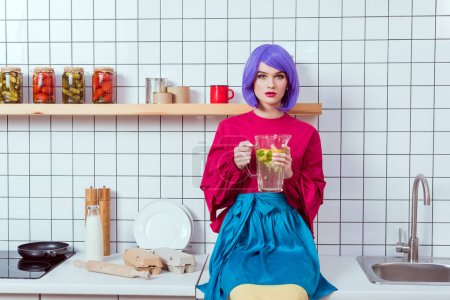 Photo for Housewife with purple hair and colorful clothes sitting on kitchen counter and holding glass jar of lemonade - Royalty Free Image