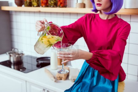 Photo for Cropped view of housewife with purple hair and colorful clothes sitting on kitchen counter and pouring lemonade in glass - Royalty Free Image