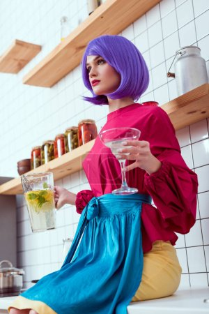 Photo for Housewife with purple hair and colorful clothes sitting on kitchen counter and holding jar of lemonade with glass - Royalty Free Image