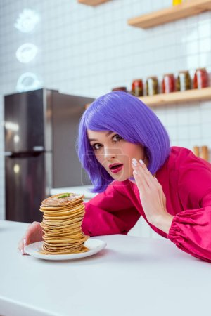 Photo for Surprised housewife with purple hair and pancakes looking at camera and gesturing with hand in kitchen - Royalty Free Image