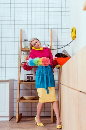 Photo for Beautiful housewife in colorful clothes holding dusting brush and talking on retro telephone in kitchen - Royalty Free Image
