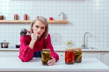 Photo for Beautiful fashionable housewife looking at camera and holding seamer with jars of pickled vegetables on kitchen counter - Royalty Free Image