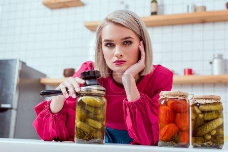 Photo pour Belle femme au foyer à la mode regardant la caméra et en tenant pour sertisseuse avec pots de légumes marinés sur le comptoir de cuisine - image libre de droit