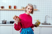 beautiful fashionable housewife holding jars of pickled vegetables and looking at camera in kitchen