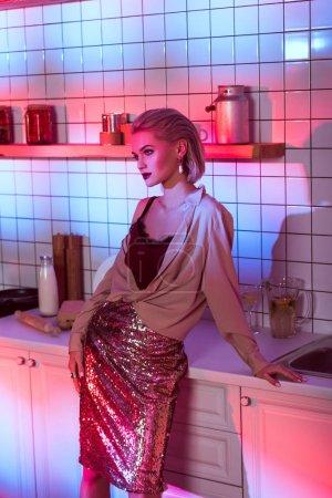 Photo pour Belle femme élégante, qui pose en cuisine avec néon rose - image libre de droit