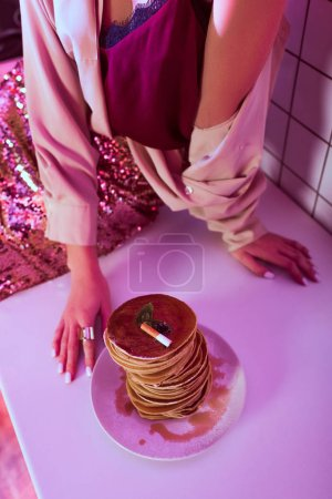 Photo for Cropped view of woman sitting on kitchen counter near plate of pancakes with cigarette ashes on top - Royalty Free Image