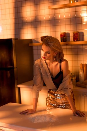 Photo for Elegant housewife leaning over counter while cooking in kitchen with orange light - Royalty Free Image