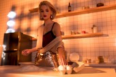 selective focus of housewife with flour on counter cooking in kitchen with orange light