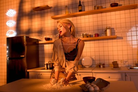 Photo for Elegant housewife with flour on counter cooking and smoking in kitchen with orange light - Royalty Free Image