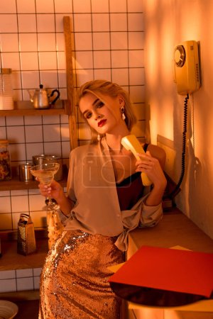 elegant woman holding retro telephone with cocktail and looking at camera in kitchen with orange light