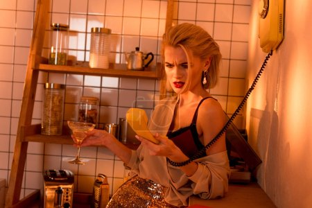 Foto de Mujer frustrada sosteniendo teléfono retro y cristal de cóctel en la cocina con luz naranja - Imagen libre de derechos