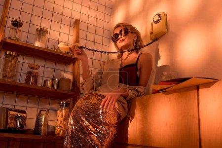 Foto de Elegante mujer en gafas de sol con teléfono retro en cocina con luz naranja - Imagen libre de derechos