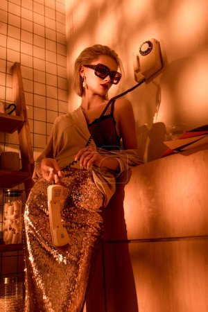 Photo for Elegant woman in sunglasses holding retro telephone in kitchen with orange light - Royalty Free Image
