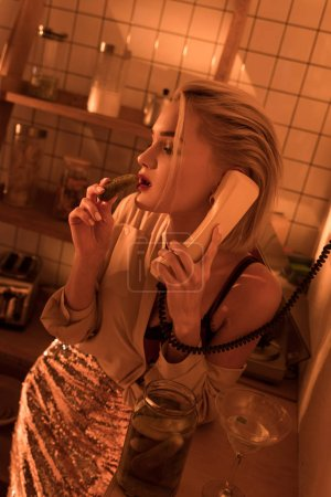 beautiful elegant woman eating pickled cucumber while talking on retro telephone in kitchen with orange light