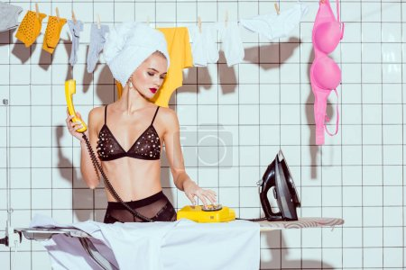 Photo for Beautiful housewife dialing retro telephone in bathroom - Royalty Free Image