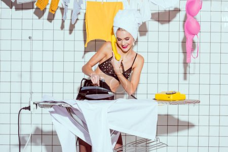 Photo for Beautiful housewife with towel on head ironing clothes and talking on retro telephone in bathroom - Royalty Free Image
