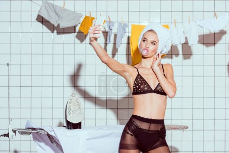 Photo pour Beautiful housewife in towel and lingerie taking selfie on smartphone and blowing bubble gum while during ironing in bathroom - image libre de droit