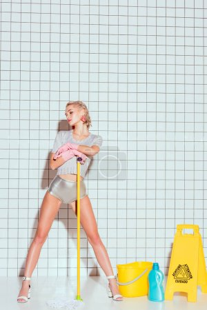 Photo for Young housewife holding mop and posing with cleaning equipment and white tile on background - Royalty Free Image