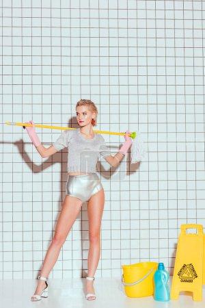 schöne Hausfrau hält Wischmopp und posiert mit Reinigungsgeräten und weißen Fliesen auf dem Hintergrund