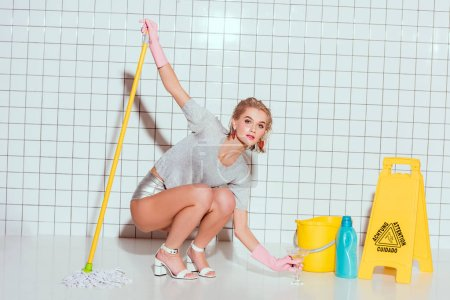 Photo for Beautiful housewife with cocktail glass and mop in bathroom - Royalty Free Image