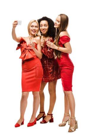 Foto de Hermosas chicas multiétnicas en vestidos rojos con copas de champagne tomando selfie en smartphone aislado en blanco - Imagen libre de derechos