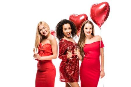 Foto de Sonrientes multiétnicas chicas lindas con globos en forma de corazón y copas de champán brindando aisladas en blanco - Imagen libre de derechos