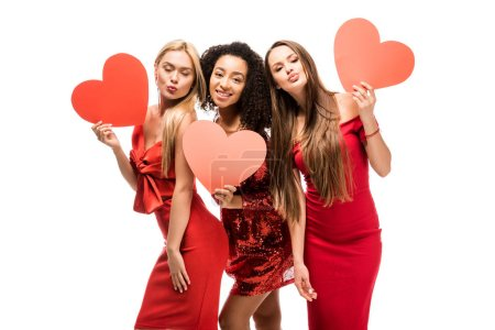 beautiful multiethnic girls holding cardboard hearts, pouting lips and posing isolated on white
