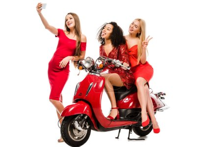 Photo for Beautiful multiethnic girls in red dresses sitting on motor scooter and taking selfie on smartphone isolated on white - Royalty Free Image