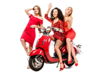 Photo for Beautiful happy multiethnic girls in red dresses posing on motor scooter isolated on white - Royalty Free Image