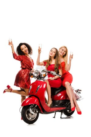 Photo for Beautiful multiethnic girls in red dresses on motor scooter cheering with champagne glasses isolated on white - Royalty Free Image