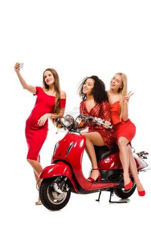 Foto de Beautiful multiethnic girls in red dresses on motor scooter taking selfie on smartphone isolated on white - Imagen libre de derechos