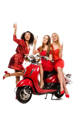 Photo for Beautiful multiethnic girls in red dresses posing on motor scooter with champagne glasses isolated on white - Royalty Free Image