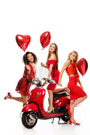 beautiful smiling multiethnic girls with heart shaped balloons and red motor scooter posing isolated on white