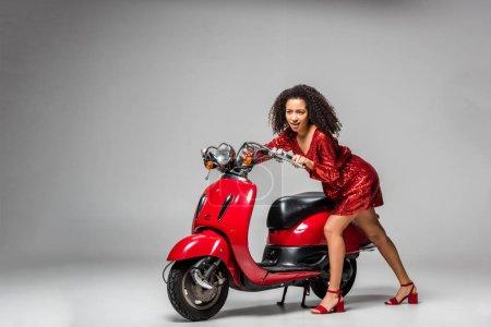 schöne afrikanisch-amerikanische Mädchen in rotem Kleid posiert mit Motorroller auf grauem Hintergrund