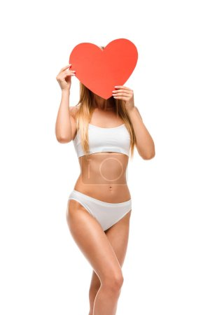 Photo for Girl in underwear holding heart shaped card in front of face isolated on white - Royalty Free Image