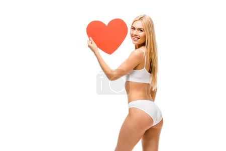 Photo for Beautiful smiling girl in underwear holding heart shaped card isolated on white - Royalty Free Image
